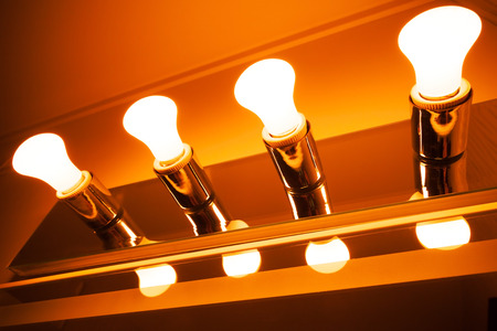 electrolier: Four shining electrical lamps in a row, modern orange toned illumination Stock Photo