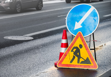 Roadsigns on the urban asphalt road. Men at work Stock Photo