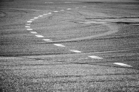 asphalt road: Abstract transportation background. White bent lines over dark rough asphalt, road marking. Selective focus with shallow DOF Stock Photo