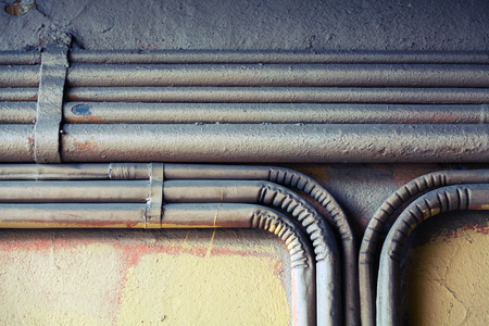 voltage gray: Abstract industrial background, group of bent vintage electrical conduits mounted on a concrete wall.  Old style toned, photo filter effect Stock Photo