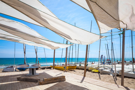sailing yacht: Awnings in sails shape covering relax area near sailing boats on the sandy beach in Calafell town, coast of Mediterranean sea, Catalonia, Spain