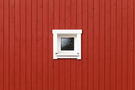 marco madera: Pared de madera roja con la peque�a ventana en el marco blanco, normalmente fragmento de arquitectura de la casa habitable escandinava Foto de archivo