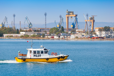 enters: Yellow and white small pilot boat enters the port of Varna, Bulgaria Editorial