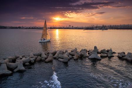 enters: Sailing yacht enters the Varna harbor at the sunset. Black Sea coast Stock Photo