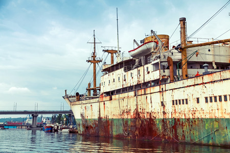 tonal: Old abandoned rusted ship stands moored in Varna port, Bulgaria. Vintage stylized photo with tonal correction filter