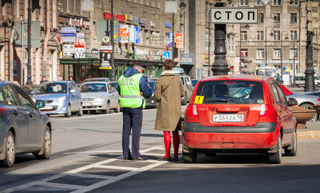 stopped: Saint-Petersburg, Russia - April 24, 2015: Russian traffic police inspector checks documents of a stopped inexperienced driver on a roadside in a big city Editorial
