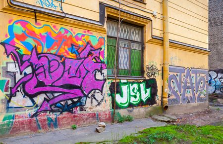 window graffiti: Saint-Petersburg, Russia - May 6, 2015: Abandoned urban courtyard with colorful abstract graffiti text on damaged wall with window. Vasilievsky island, Central part of St. Petersburg