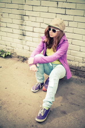 tonal: Beautiful teenage girl in cap and sunglasses sits on a skateboard near brick wall, vertical photo with warm retro tonal correction effect Stock Photo