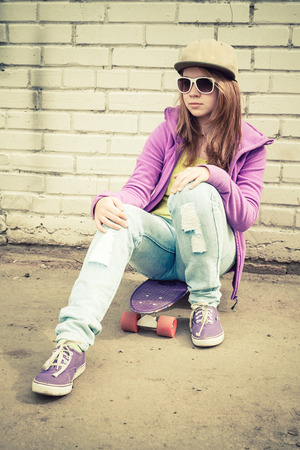 tonal: Beautiful teenage girl in cap and sunglasses sits on a skateboard near urban brick wall, vertical photo with warm retro tonal correction effect