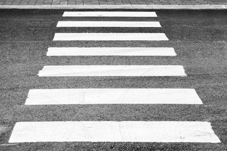 Pedestrian crossing road marking, white rectangles over gray asphalt pavement, perspective view with shallow DOF