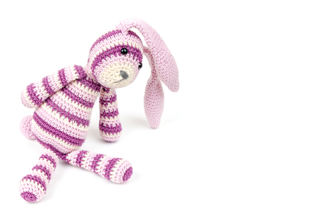 Knitted rabbit toy sits isolated on white background, selective focus with shallow DOF photo
