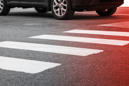 bad accident: Pedestrian crossing road marking and moving car, photo with red gradient tonal filter, selective focus and shallow DOF Stock Photo