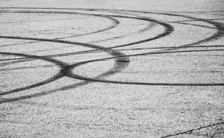 track marks: Abstract transportation background with dark tire tracks on gray asphalt road, selective focus with shallow DOF