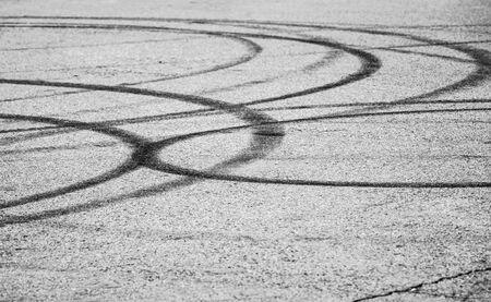 llantas: Transporte de fondo abstracto con las huellas de los neumáticos oscuras en carretera de asfalto gris, foco selectivo con el DOF bajo