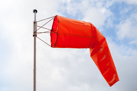 windsock: Windsock. Red wind indicator over blue cloudy sky Stock Photo