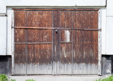 Old locked wooden gate in white concrete wall of an ordinary living house photo