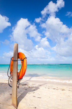 beach buoy: Red life buoy hanging on wooden pole, empty sandy beach of Dominican republic