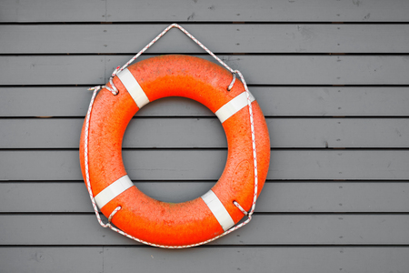 lifebuoy: Red lifebuoy hanging on gray wooden wall of a port building Stock Photo