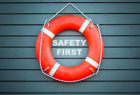 cinturon seguridad: Seguridad primero. Colgante salvavidas rojo en la pared de madera azul de un edificio puerto con la etiqueta de texto Foto de archivo