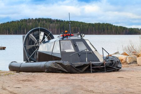 hovercraft: Black modern hovercraft is laying on the sandy coast of Saimaa lake in Finland