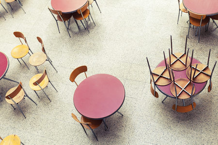 round chairs: Round tables and chairs stand in empty cafe interior, top view, vintage toned photo