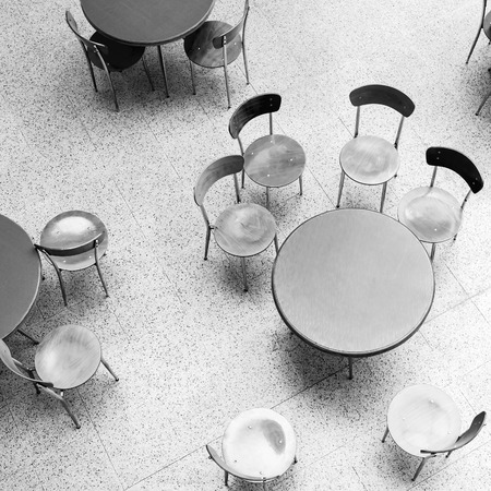 round chairs: Round tables and chairs stand in empty cafe interior, top view monochrome square photo