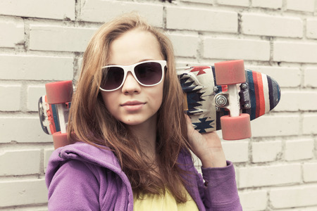 tonal: Blond teenage girl in sunglasses holds skateboard near gray urban brick wall, vintage tonal correction, old style photo filter effect