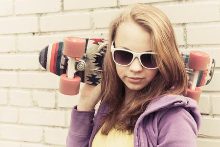 tonal: Blond teenage girl in sunglasses holds skateboard near gray urban brick wall, vintage tonal correction, old style filter effect