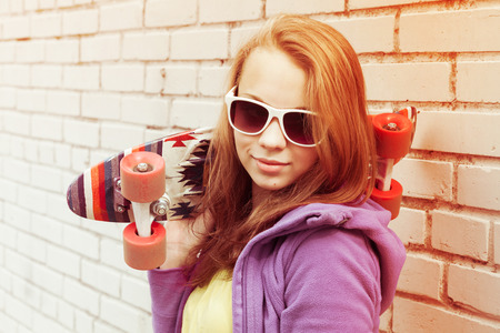 tonal: Blond teenage girl in sunglasses holds skateboard near gray urban brick wall, bright tonal correction, old style filter effect Stock Photo