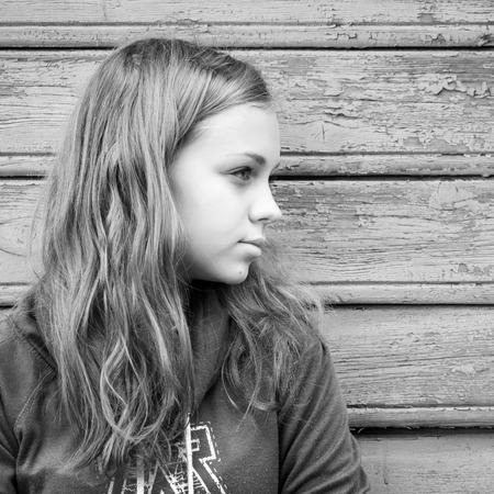 kinderen: Mooie blonde blanke meisje tiener, close-up outdoor portret over landelijke houten wand