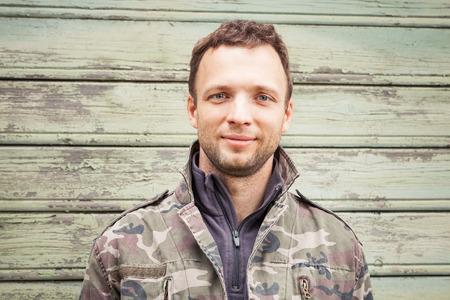 Young Caucasian man in camouflage outdoor portrait over green rural wooden wall 版權商用圖片