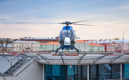 heliport: Saint-Petersburg, Russia - May 07, 2015: Small blue helicopter stands on the floating helipad on the Neva river in central part of Petersburg