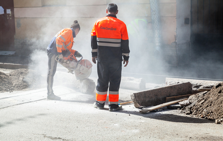 stone cutter: Saint-Petersburg, Russia - May 32, 2015: men at work, urban road under construction, sawing of a roadside border stones