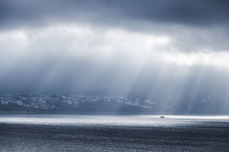 Volume sunlight goes through dark stormy clouds. Bay of Tangier, Morocco, Africa