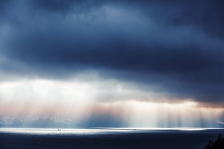 ourdoor: Volume sunlight goes through dark blue stormy clouds. Bay of Tangier, Morocco, Africa Stock Photo