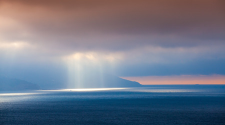 Volume sunlight goes through dark clouds. Bay of Tangier, Morocco, Africa photo