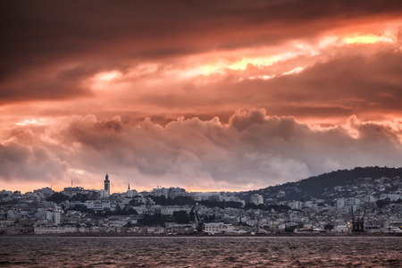 ourdoor: Bright red sunset sky over Tangier city Morocco. High contrast red tonal correction photo filter effect