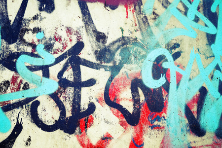 Abstract colorful graffiti patterns over old urban concrete wall, vintage tonal photo filter effect, retro style