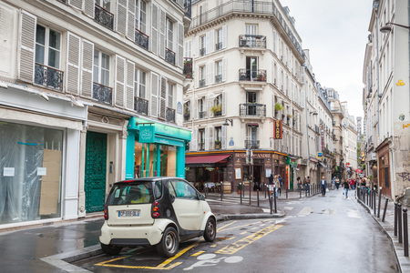 street corner: Paris France August October 2014: small white Smart car stands on the street in Paris tourists walk on Rue St. Andre Des Arts