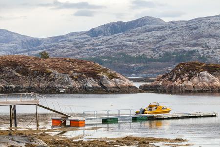 motor boat: Rural Norwegian coastal landscape. Small motor boat stands moored near floating pier Stock Photo