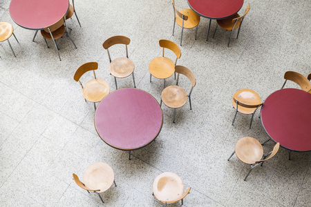 round chairs: Round tables and chairs around stand in an empty cafe interior, top view