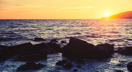 ourdoor: Coastal stones and water, sunset on the Atlantic ocean coast in Morocco, Tangier. Vintage tonal correction photo filter, instagram old style