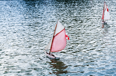 pleasure ship: Traditional small wooden sailing toy boats in the pond of park Jardin du Luxembourg, Paris, France Stock Photo