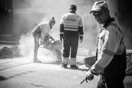 Saint-Pétersbourg, Russie - 23 mai 2015: des hommes au travail, routier urbain en cours de construction, le sciage de pierres frontaliers routiers, photo noir et blanc avec mise au point sélective sur la scie et shallow DOF Banque d'images - 40599556