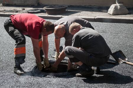 asphalting: Saint-Petersburg, Russia - May 30, 2015: men at work, urban road under construction, asphalting in progress, workers install sewer manhole