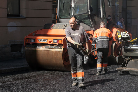 asphalting: Saint-Petersburg, Russia - May 30, 2015:  men at work, urban road under construction, asphalting in progress with workers, asphalter and roller