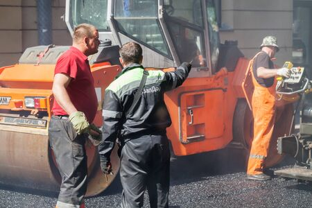 asphalting: Saint-Petersburg, Russia - May 30, 2015: men at work, urban road under construction, asphalting in progress, worker talks with quality controller Editorial