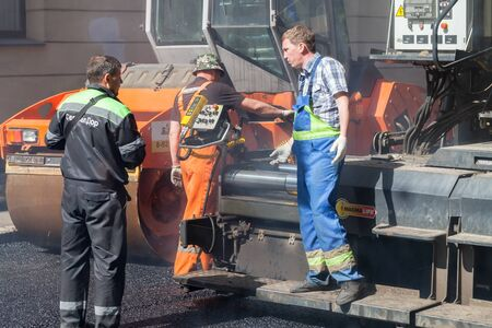 asphalting: Saint-Petersburg, Russia - May 30, 2015: men at work, urban road under construction, asphalting in progress, quality control manager talks with paver operator