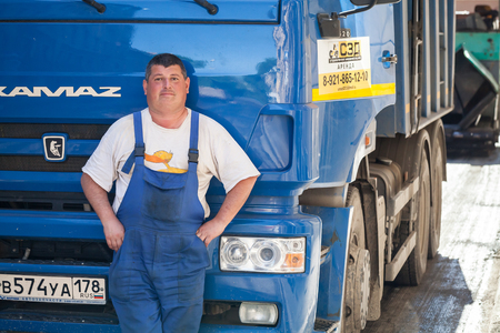 Saint-Petersburg, Russia - May 30, 2015: Positive truck driver stands near his Kamaz lorry cabin Editorial