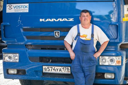 trucker: Saint-Petersburg, Russia - May 30, 2015: Positive truck driver stands near his blue Kamaz lorry cabin